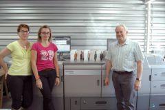 Les deux opératrices PAO et Yannick Garet le directeur de l'imprimeur prennent la pose devant la Linoprint d'Heidelberg.
