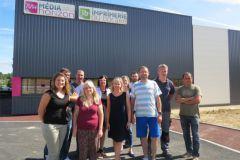 Une partie de l'équipe de l'Imprimerie du Bocage (avec la directrice générale au centre) devant leur nouveau bâtiment.